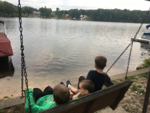 Three young children, boys, are seated on a bench swing facing away from the camera.  They are all looking across a small lake with the other side in the distance.